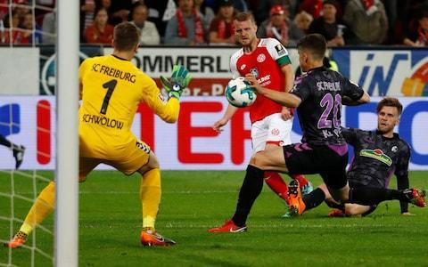 "A bizarre video assistant referee (VAR) decision caused mayhem in a Bundesliga game on Monday night when two teams were ordered back on to the pitch at half time because the referee decided to award a penalty after watching a replay on TV. Players of Mainz 05 and Freiburg were astonished when referee Guido Winkmann was notified by video referee Bibiana Steinhaus, who was watching in Cologne, that he should check a replay of a handball incident just before his half-time whistle. Winkmann watched the incident again on the pitchside screen and evidently decided Freiburg's Marc Oliver Kempf had deliberately put his hand to the ball. He ordered the players back onto the pitch much to the bemusement of Freiburg coach Christian Streich, who was seen shaking his head in disbelief. ""We're not going out,"" said Streich as he led his confused players back into the changing room. Some were looking at TVs to determine exactly what was going on. Marc-Oliver Kempf was adjudged to have handled the ball by video referee Bibiana Steinhaus Credit: REUTERS The Freiburg team eventually emerged back onto the pitch, where Winkmann explained to Streich that it was a penalty for the home side. Pablo de Blasis, who had to wait for Alexander Schwolow to retake his place in goal, held his nerve to score inside the left corner as the Freiburg keeper dived the other way. ""We thought that when the whistle goes for half time, that the first 45 minutes are ticked off,"" Freiburg sporting director Jochen Saier told Eurosport at half time. ""That wasn't the case in this scene, we have to accept that with heavy hearts. Things are getting stranger."" Pablo de Blasis kept his cool to score the controversial 'half-time' penalty Credit: REUTERS Kempf, who conceded the spot-kick, was substituted at half time. There was a further 10-minute delay before the start of the second half as fans threw hundreds of toilet rolls onto the pitch in a protest against Monday evening matches. Many German fans have opposed the introduction of Monday games, saying matches should be played at the weekend when most supporters can attend. Protests have taken place during most Monday games. Mainz went on to win the fixture 2-0."