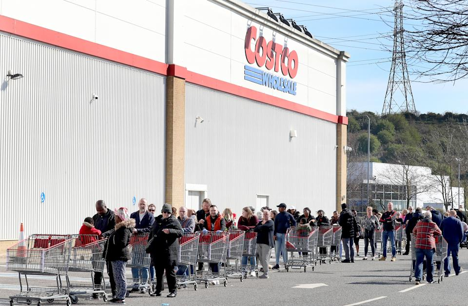 Customers queue to shop at Costco in Thurrock, Essex, the day after Prime Minister Boris Johnson put the UK in lockdown to help curb the spread of the coronavirus. (Photo by Gareth Fuller/PA Images via Getty Images)