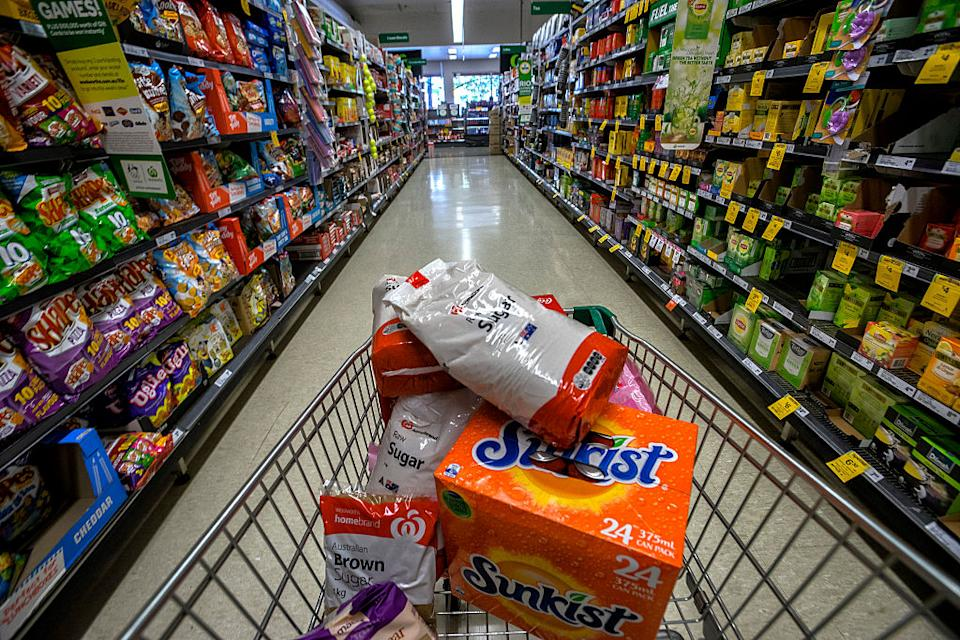 Groceries are pictured in a trolley in a Woolworths supermarket aisle.
