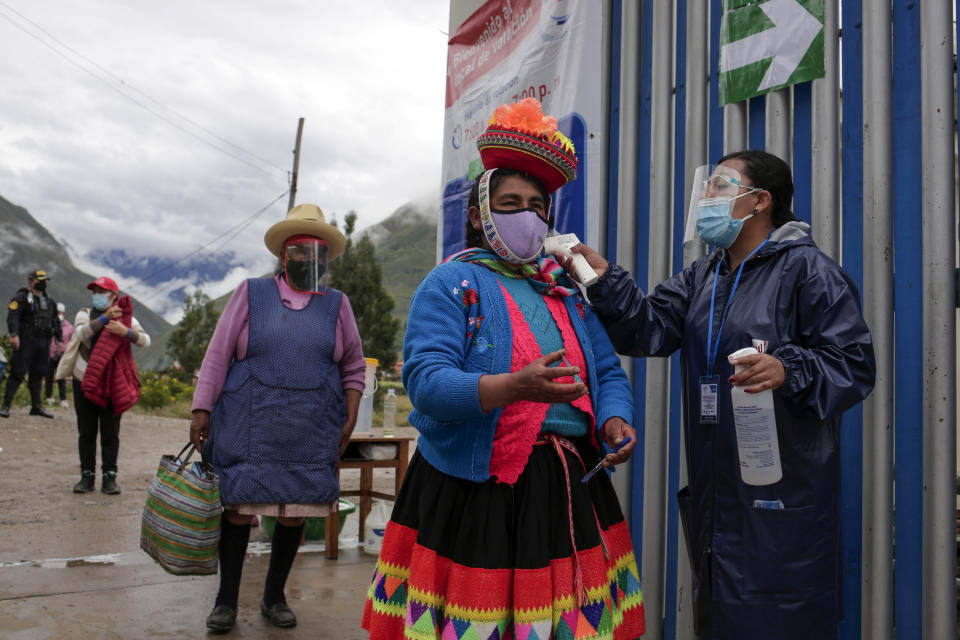 Voters wearing masks to curb the spread of the new coronavirus have their temperature measured at the entrance of a polling station during general elections in Ollantaytambo, Peru, Sunday, April 11, 2021. (AP Photo/Sharon Castellanos)