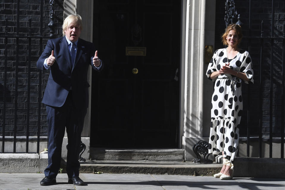 Britain's Prime Minister Boris Johnson and Annemarie Plas, founder of Clap For Our Carers, join in the pause for applause to salute the NHS 72nd birthday, outside 10 Downing Street in London, Sunday, July 5, 2020. People across the U.K. joined a round of applause to celebrate the 72nd anniversary of the formation of the free-to-use National Health Service, undoubtedly the country's most cherished institution. The reverence with which it is held has been accentuated this year during the coronavirus pandemic. (Victoria Jones/PA via AP)