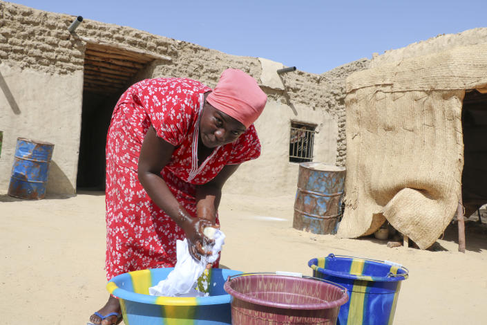 Zahra Abdou washes laundry in Timbuktu, Mali, Wednesday. Sept. 29, 2021. It's been nine years since Islamic extremists in northern Mali arrested Abdou on charges of showing her hair and wearing an outfit they said was too tight. The trauma still torments her, she says. Her anxiety has increased since France announced in July that it will reduce its 5,000 troops in Mali to about 3,000 by 2023 after years of leading the fight against jihadism in Mali's north. (AP Photo/Moulaye Sayah)