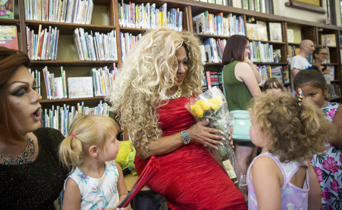 Vanessa Carr, center, receives flowers from Katherine Lockhart, 4, right, as Carr and Blazen Haven, left, meet Lockhart and Lucille O'Steen, 2, second from left, during Drag Queen Story Time at the Alvar Library in New Orleans on Saturday, Aug. 25, 2018. Children and parents and caregivers packed into the library to hear stories and sing songs during the event. (Scott Threlkeld/The Advocate via AP)