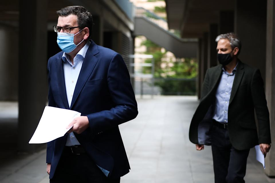 MELBOURNE, AUSTRALIA - AUGUST 17: Premier of Victoria Daniel Andrews (left) and Victorian Chief Health Officer, Brett Sutton (right) arrive for the press conference on August 17, 2021 in Melbourne, Australia. Lockdown restrictions have been extended for another two weeks across Melbourne as Victoria continues to record new cases of the highly infectious COVID-19 Delta variant. A curfew is also now in place from 9 pm to 5 am each night across the metropolitan area. The new restrictions will remain in place until 11.59 pm on Thursday, 2 September. (Photo by Asanka Ratnayake/Getty Images)