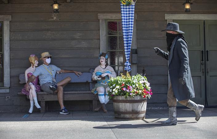 William Bishop sits with two female statues and performer Clay Mayfield in a western outfit walks near him.