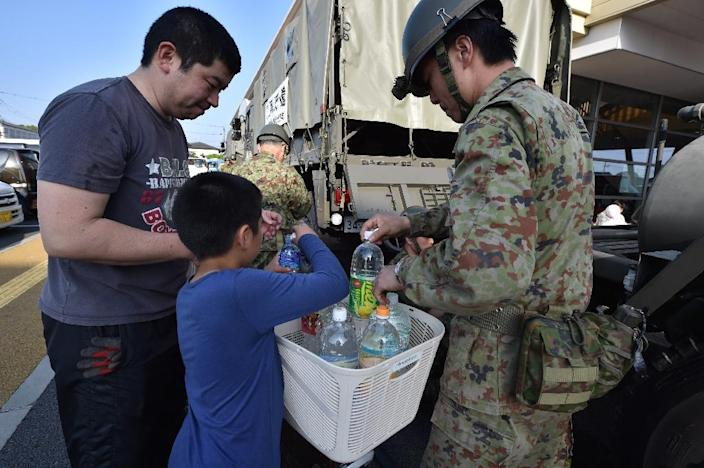 A Self-Defense Forces personnel helps a family to pack bottles of water in Mashiki, Kumamoto prefecture on April 15, 2016, after a 6.5-magnitude quake struck the southwestern island of Kyushu (AFP Photo/Kazuhiro Nogi)