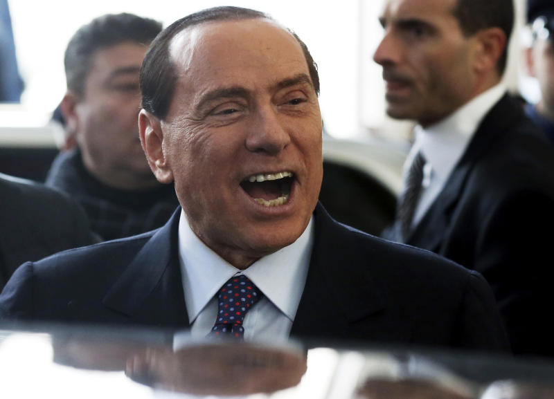 """FILE - In this Dec. 29, 2012 file photo Silvio Berlusconi smiles as he arrives at Milan's central train station. Former Premier Silvio Berlusconi announced a deal Monday, Jan. 7, 2013 with the Northern League, his fractious coalition partner in three governments, to jointly run in Italy's election next month. The move could give fresh impetus to the center-right and extend the Berlusconi era. While leaving open the question of whether he will run himself, Berlusconi underlined his ambitions for the deal reached overnight at his villa near Milan by saying: """"Habemus Papum,"""", the Latin phrase for """"We have a pope."""" (AP Photo/Luca Bruno)"""