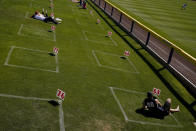 Fans watch from a boxes painted on the grass to promote social distancing during the fifth inning of a spring training baseball game between the Seattle Mariners and the Cleveland Indians on Tuesday, March 2, 2021, in Peoria, Ariz. (AP Photo/Charlie Riedel)