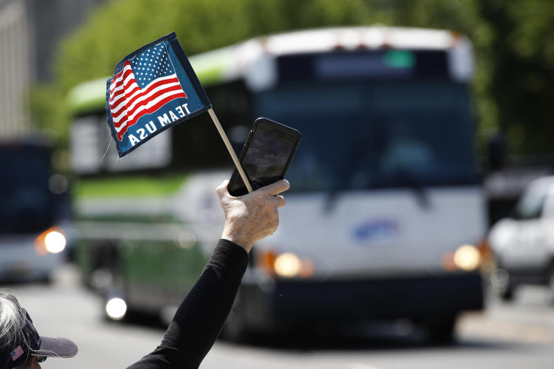 """FILE - In this May 13, 2020, file photo, tour guide Barbara Western waves a flag in support of bus and motor coach operators as they circle the National Mall in Washington. As a candidate for the White House, President Donald Trump once said he wanted """"whatever is best"""" for the residents of the nation's capital. But over the course of his more than three years in office a disconnect between the president and District of Columbia has emerged -- a chasm that has only grown during the coronavirus pandemic. (AP Photo/Patrick Semansky, File)"""