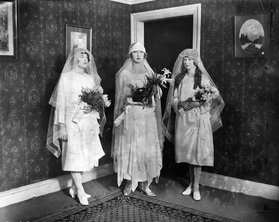 <p>Three models wear wedding dresses typical of the 1920s, with slim lines, short hemlines, and cloche veils. </p>