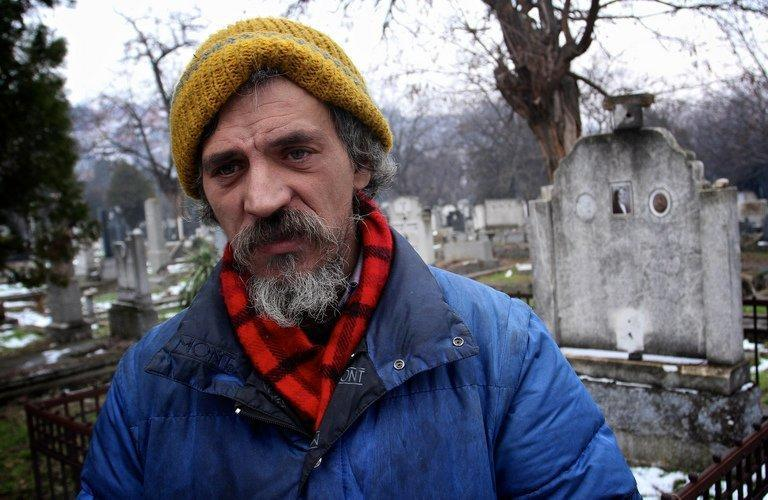 Homeless Bratislav Jovanovic, 43, stands on January 10, 2013 beside a tomb at a cemetery in Nis, Serbia. Jovanovic has been homeless for nearly twenty years, since his house was burned down in a fire. The last 15 years he has lived in a tomb beside the caskets of dead relatives
