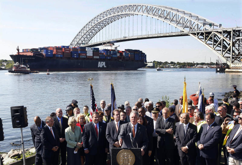 FILE - In this Tuesday, Sept. 21, 2010 file photo, the President Truman, a large cargo ship, passes under the Bayonne Bridge in Bayonne, N.J., as New Jersey Gov. Chris Christie, third left, front, and Lt. Gov. Kim Guadagno, fourth left, front, listen with others, as U.S. Rep. Albio Sires (D-NJ) talks about plans to raise the height of the bridge to accommodate the larger next generation of cargo ships.  Residents in N.J. cities and towns are leery of the monster ships that will soon arrive because of a trade project thousands of miles away they believe will harm their air quality, roadways and waterways. (AP Photo/Mel Evans,file)