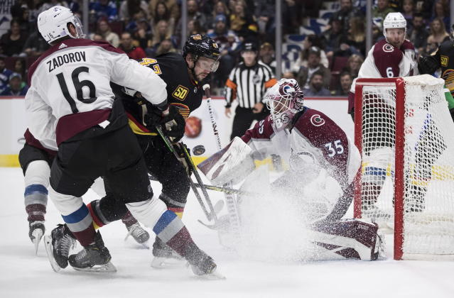 Colorado Avalanche goalie Antoine Bibeau, right, stops Vancouver Canucks' Sven Baertschi, center, of Switzerland, as Colorado's Nikita Zadorov (16), of Russia, defends during the second period of an NHL hockey game Saturday, Nov. 16, 2019, in Vancouver, British Columbia. (Darryl Dyck/The Canadian Press via AP)