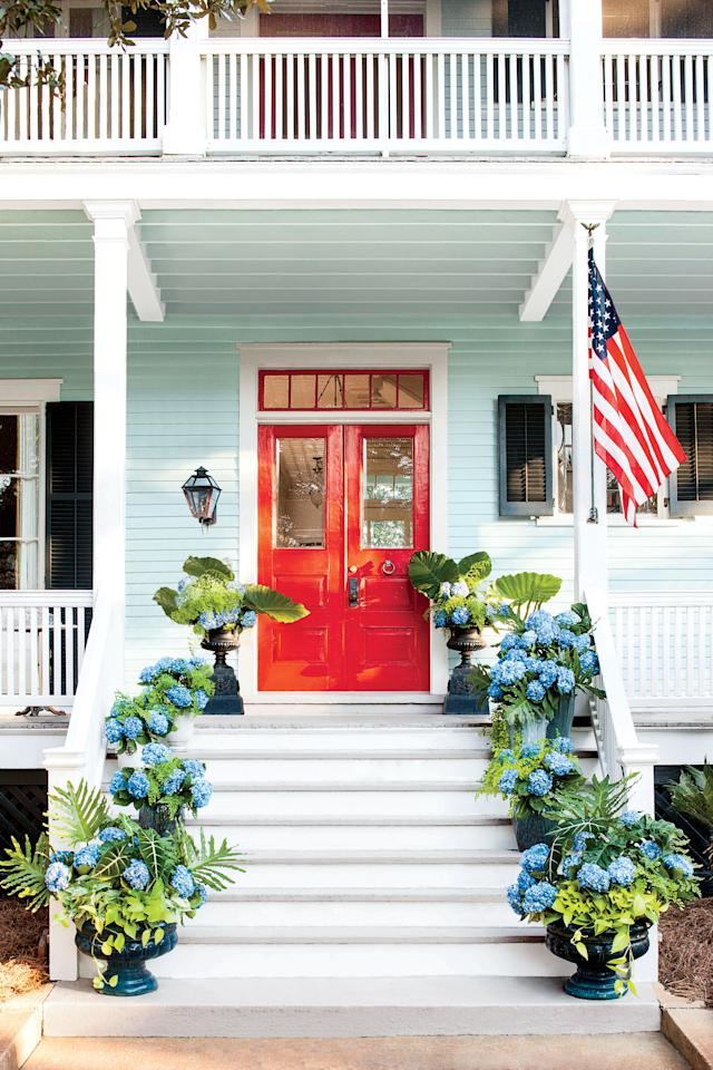"""<p>This front entrance and walkway is the epitome of patriotic pride. Glossy red double doors, crisp white trim, and pots of blue <a rel=""""nofollow"""" href=""""http://www.southernliving.com/garden/flowers/caring-for-hydrangeas"""">hydrangeas</a> form to make a beautiful, all-American palette for the start of summer. </p>"""