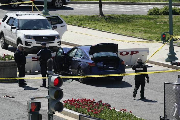 U.S. Capitol Police officers stand near a car that crashed into a barrier on Capitol Hill in Washington
