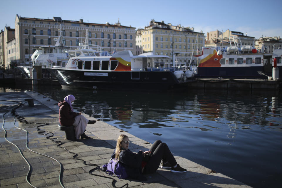 "Girls rest on the port of Marseille, southern France, Wednesday, Feb. 10, 2021. More than three dozen police officers descended on a small private school in Paris, blocked students inside their classrooms, took photos everywhere, even inside the refrigerator, and grilled the school director in her office. The dragnet sweeps schools, shops, clubs or mosques to rout out ""radicalization. (AP Photo/Daniel Cole)"