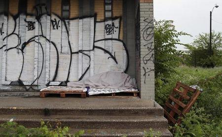 A homeless person sleeps under a blanket on the porch of a shuttered public school covered with graffiti in a once vibrant southwest neighborhood in Detroit,