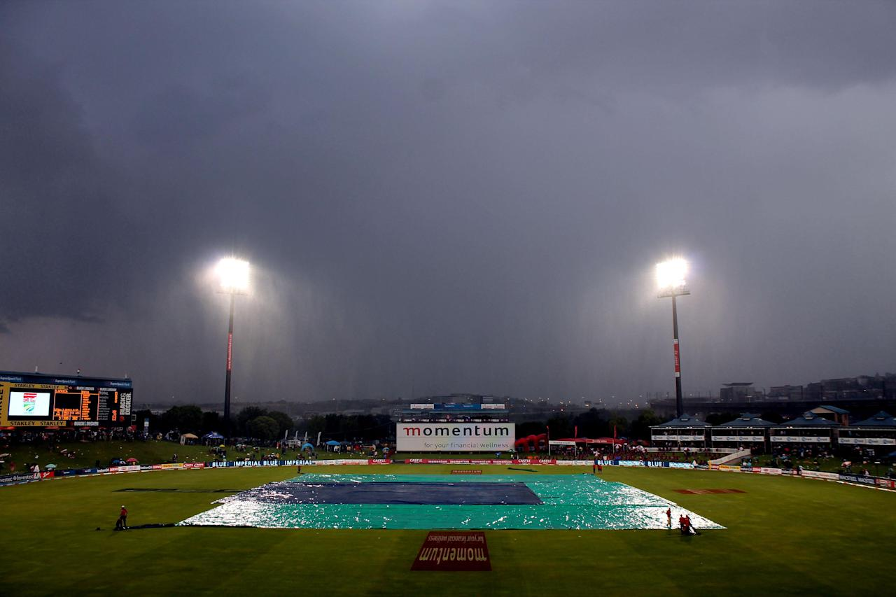 Ground staff cover the pitch at at Super Sport Park as rains interrupt the 3rd ODI match between India and South Africa in Centurion on Dec.11, 2013. (Photo: IANS)