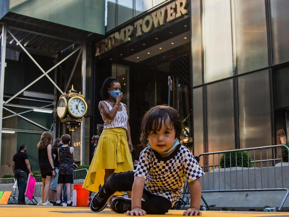 "A baby boy sits on the ""Black Lives Matter"" mural in front of Trump Tower in New York on July 9, 2020. <p class=""copyright"">Pablo Monsalve/VIEWpress via Getty Images</p>"