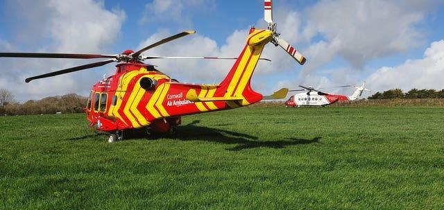 A Cornwall Air Ambulance helicopter (left) alongside a Coastguard SAR helicopter in a field adjacent to where a Royal Navy Hawk jet crashed in woodland in Cornwall after the two pilots ejected