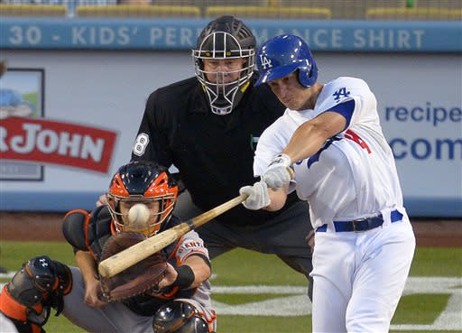 Los Angeles Dodgers' Mark Ellis, right, hits a two-run home run as San Francisco Giants' Buster Posey catches and home plate umpire D.J. Rayburn watches during the third inning of a baseball game, Tuesday, June 25, 2013, in Los Angeles. (AP Photo/Mark J. Terrill)