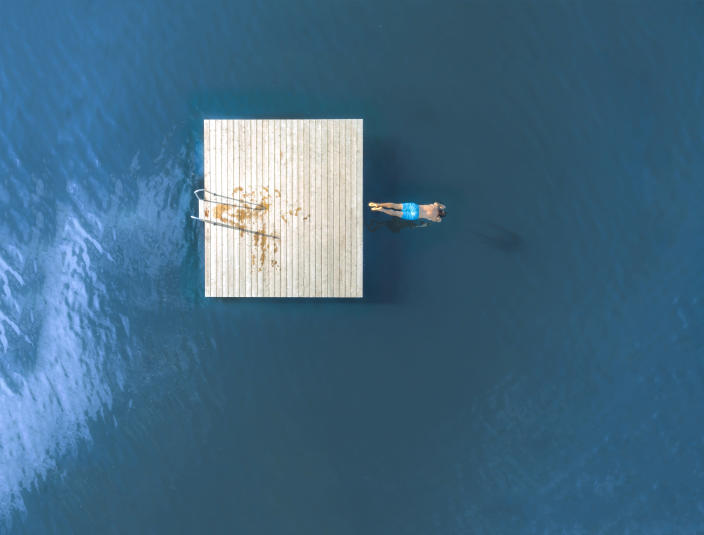 Image of a man jumping from a floating dock into a lake.