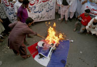 Supporters of a religious group burn defaced images of French President Emmanuel Macron with a representation of a French flag during a protest against the French president and republishing of caricatures of the Prophet Muhammad they deem blasphemous, in Karachi, Pakistan, Saturday, Oct. 31, 2020. Muslims have been calling for both protests and a boycott of French goods in response to France's stance on caricatures of Islam's most revered prophet. (AP Photo/Fareed Khan)