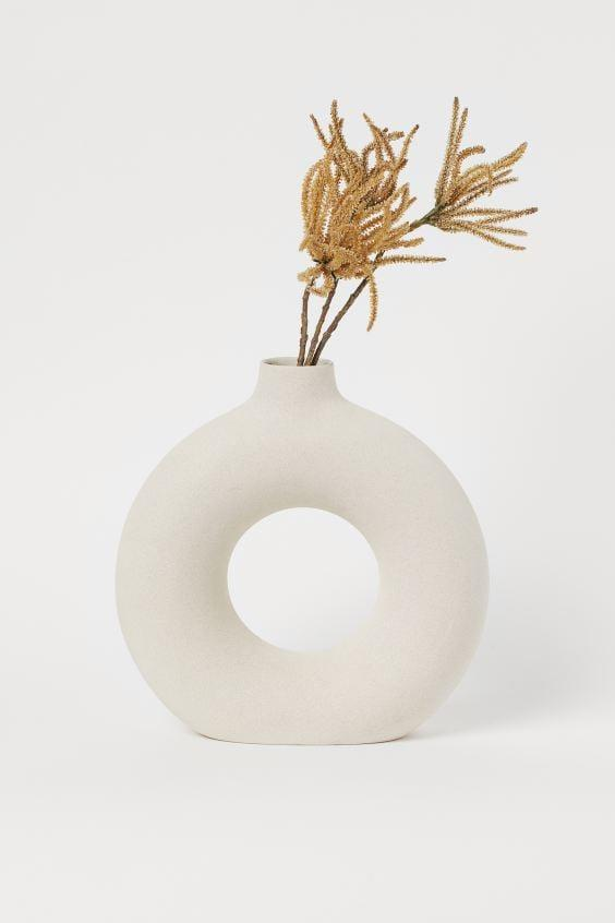"<p>Put this <a href=""https://www.popsugar.com/buy/HampM-Large-Ceramic-Vase-560411?p_name=H%26amp%3BM%20Large%20Ceramic%20Vase&retailer=www2.hm.com&pid=560411&price=35&evar1=casa%3Aus&evar9=46598422&evar98=https%3A%2F%2Fwww.popsugar.com%2Fhome%2Fphoto-gallery%2F46598422%2Fimage%2F47342595%2FHM-Large-Ceramic-Vase&list1=shopping%2Chome%20decor%2Chome%20shopping&prop13=mobile&pdata=1"" rel=""nofollow"" data-shoppable-link=""1"" target=""_blank"" class=""ga-track"" data-ga-category=""Related"" data-ga-label=""https://www2.hm.com/en_us/productpage.0812789001.html"" data-ga-action=""In-Line Links"">H&amp;M Large Ceramic Vase</a> ($35) on an end table.</p>"