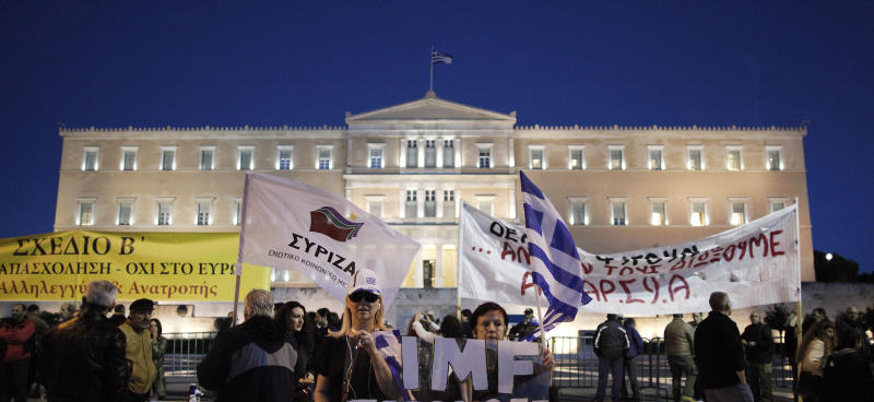 Demonstrators hold national and Syriza's party flag as well with anti austerity banners  outside of the Greek Parliament in Athens on Sunday Nov. 11, 2012.  Greece's lawmakers were set  on Sunday to pass next year's austerity budget, extending tough spending cuts measures that have already left Greeks struggling as the country tries to slash its debts and pull itself out of a severe recession. (AP Photo/Petros Giannakouris)