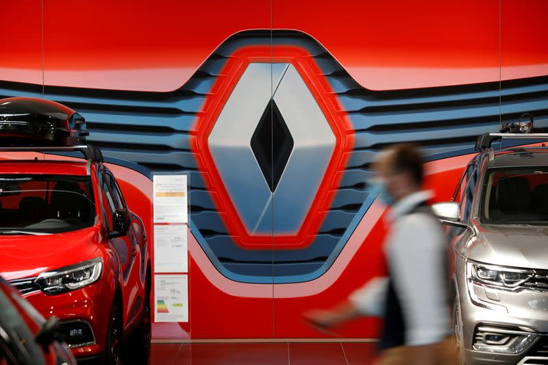 FILE PHOTO: An employee walks past a logo of Renault at a dealership in Nantes