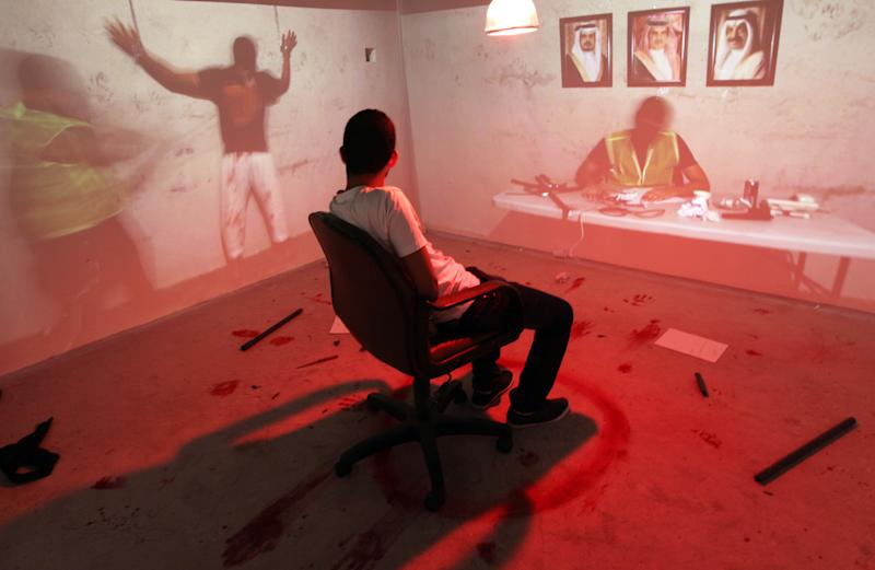 In this picture taken Monday, Oct. 28, 2013, a Bahraini man sits handcuffed in a mock torture room allegedly similar to what prisoners faced in prisons, while visiting an interactive museum-style exhibition opened by an opposition group in Manama, Bahrain. Riot police in Bahrain stormed the exhibition on Wednesday, Oct. 30, that is dedicated to the Arab Spring-inspired uprising in the violence-wracked Gulf nation where crackdowns have strained ties between the ruling dynasty and their allies in Washington and elsewhere in the West. Pictures of Bahraini leaders seen on the wall, are left to right, Crown Prince Salman bin Hamad Al Khalifa, King Hamad bin Isa Al Khalifa and Prime Minister Khalifa bin Salman Al Khalifa. (AP Photo/Hasan Jamali)