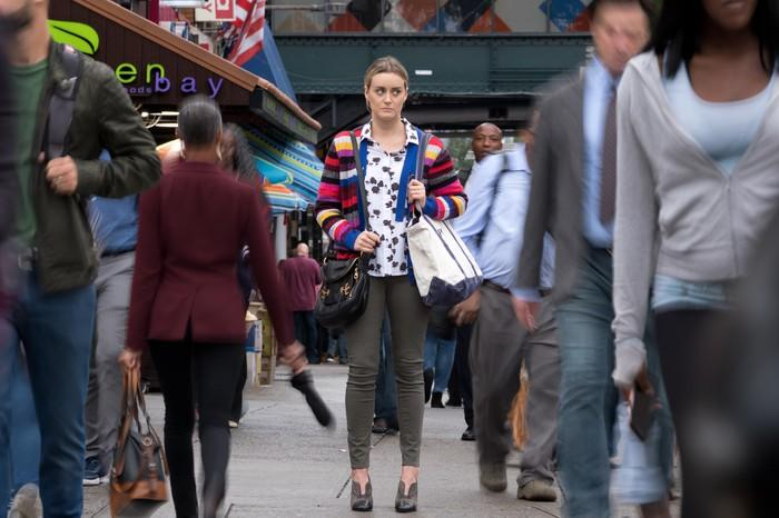 A woman standing in a crowded street as throngs of pedestrians pass her on both sides.