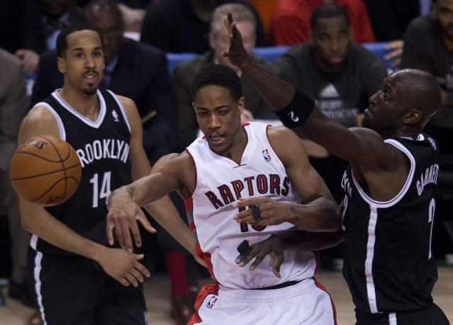 Toronto Raptors guard DeMar DeRozan, center, moves the ball past Brooklyn Nets forward Kevin Garnett, right, and Shaun Livingston (14) during the second half of Game 5 of the opening-round NBA basketball playoff series in Toronto, Wednesday, April 30, 2014. (AP Photo/The Canadian Press, Nathan Denette)