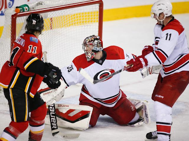 Carolina Hurricanes goalie Justin Peters, centre, looks back as the winning goal goes in the net as Calgary Flames' Mikael Backlund, left, from Sweden, and Hurricanes' Jordan Staal look on during overtime NHL hockey action in Calgary, Alberta, Thursday, Dec. 12, 2013. The Calgary Flames beat the Carolina Hurricanes 2-1. (AP Photo/The Canadian Press, Jeff McIntosh)