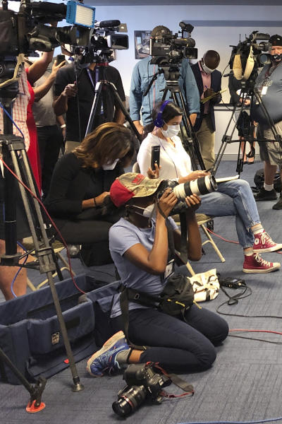 Atlanta Journal-Constitution staff photojournalist Alyssa Pointer, kneeling, works during a news conference, Tuesday, June 2, 2020, in Atlanta. Pointer was detained by officers of the Georgia Department of Natural Resources during a protest in downtown. Pointer said her press badge was clearly displayed, and she identified herself to law enforcement. (AP Photo/Kate Brumback)