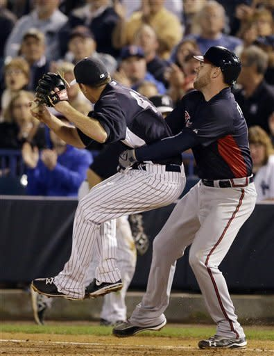 Atlanta Braves' Freddie Freeman, right, hangs on to New York Yankees' David Phelps after the two collided at first base on Freeman's ground out during the third inning of a spring training exhibition baseball game, Tuesday, March 5, 2013, in Tampa, Fla. (AP Photo/Matt Slocum)