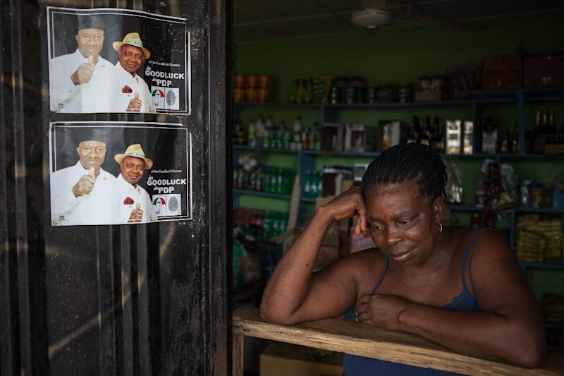 A woman on April 1, 2015 in her shop next to campaign posters of former Nigerian President Goodluck Jonathan, in Otuoke (AFP Photo/Florian Plaucheur)
