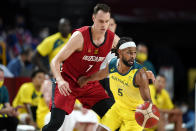 Australia's Patty Mills (5) drives around Germany's Johannes Voigtmann (7) during a men's basketball preliminary round game at the 2020 Summer Olympics, Saturday, July 31, 2021, in Saitama, Japan. (AP Photo/Charlie Neibergall)