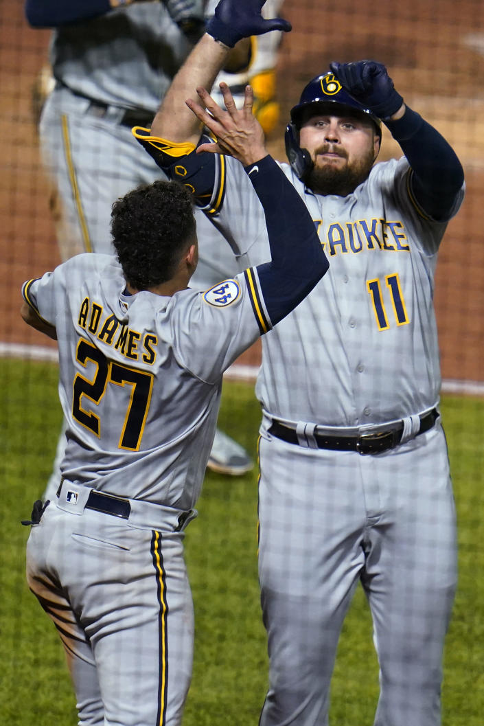 Milwaukee Brewers' Rowdy Tellez (11) celebrates with Willy Adames (27) after hitting a solo home run off Pittsburgh Pirates relief pitcher Chris Stratton during the seventh inning of a baseball game in Pittsburgh, Thursday, July 29, 2021. (AP Photo/Gene J. Puskar)