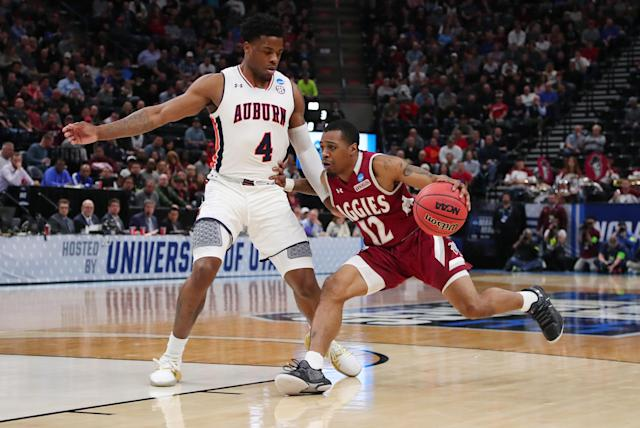 <p>AJ Harris #12 of the New Mexico State Aggies drives to the basket against Malik Dunbar #4 of the Auburn Tigers during the first half in the first round of the 2019 NCAA Men's Basketball Tournament at Vivint Smart Home Arena on March 21, 2019 in Salt Lake City, Utah. (Photo by Tom Pennington/Getty Images) </p>
