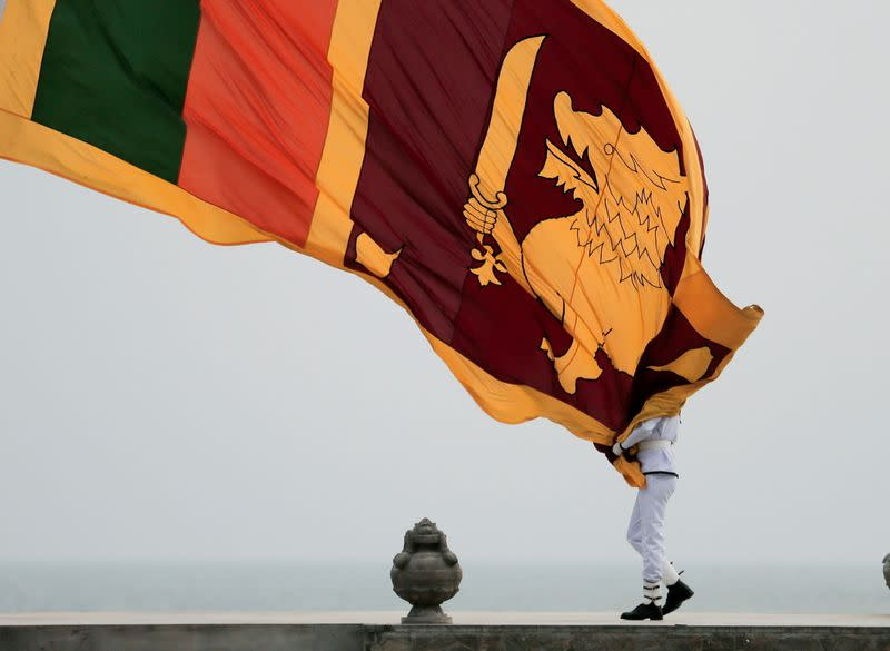 Sri Lankan military officer lowers the national flag in Colombo