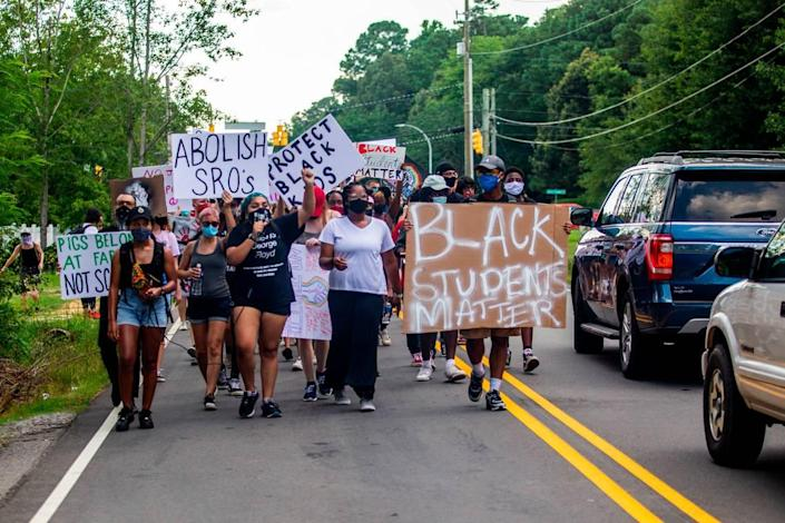 Demonstrators led by the Wake County Black Student Coalition march along Dillard Drive in Raleigh while demanding the Wake County Public School System remove the school resource officer program Tuesday, July 14, 2020. A march and sit-in coincided with a Wake County School Board meeting.