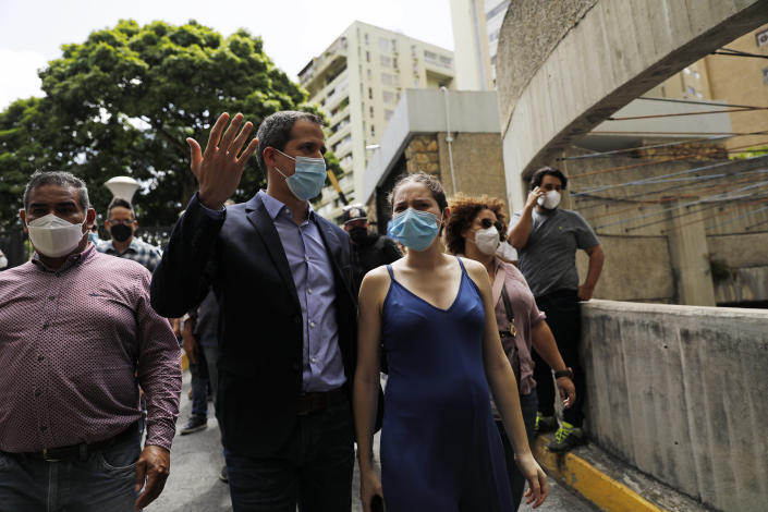 Opposition leader Juan Guaido and his wife Fabiana Rosales walk at their residential building after holding an impromptu press conference in Caracas, Venezuela, Monday, July 12, 2021. Guaido said security forces threatened his driver when he and his driver arrived home Monday. (AP Photo/Ariana Cubillos)