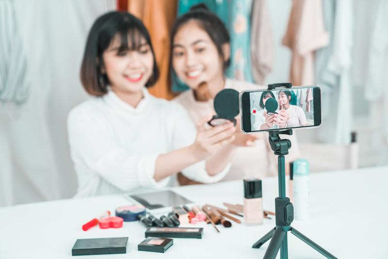 Two young women use social media to demonstrate cosmetics. (Photo: Getty)