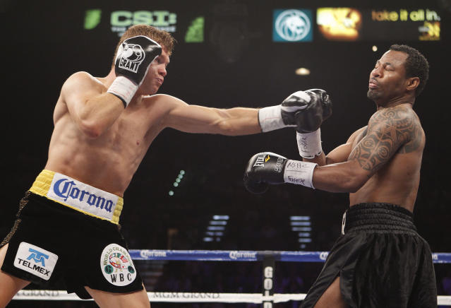 Canelo Alvarez, left, throws a punch against Shane Mosley in the first round during a WBC super welterweight title fight, Saturday, May 5, 2012, in Las Vegas. (AP Photo/Eric Jamison)