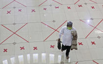 A Muslim walks across marks used to space worshippers apart as a precaution against the coronavirus after Friday prayer at the Al Barkah Grand Mosque in Bekasi on the outskirts of Jakarta, Indonesia, Friday, May 29, 2020. Muslims in some parts of Indonesia attended Friday prayers as mosques closed by the coronavirus for weeks were allowed to start reopening in the world's most populous Muslim nation. (AP Photo/Achmad Ibrahim)