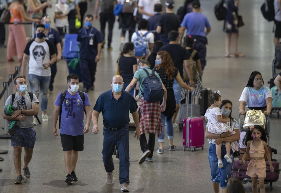 Travelers walk in a passenger terminal at Guarulhos International Airport in Guarulhos, near Sao Paulo, Brazil, Wednesday, Dec. 30, 2020, amid the COVID-19 pandemic. Despite rising infection numbers in the country, Brazilians are flocking to airports and taking to the highways to visit friends and loved ones to usher in the new year and take advantage of a long weekend. (AP Photo/Andre Penner)