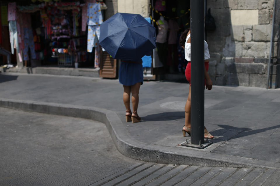 """Sex workers wait for clients on a corner in central Mexico City, Saturday, March 6, 2021. Elvira Madrid, who leads the activist group Brigada Callejera or """"The Street Brigade"""", said that her group found 15,200 sex workers on the city's streets in August 2020, about 40% more than had worked in the trade before the coronavirus pandemic hit. (AP Photo/Rebecca Blackwell)"""