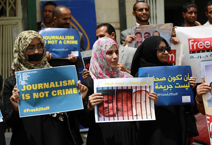 Yemenis, some of them being journalists, hold signs during a protest on June 25, 2014 in the capital Sanaa in solidarity with Al-Jazeera journalists (seen on the posters) jailed in Egypt (AFP Photo/Mohammed Huwais)