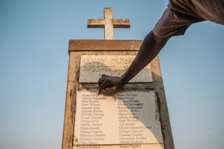 Olanyia Mohammed, 38, escaped a massacre in his village but lost 15 members of his family. He points at his parents names etched on a memorial